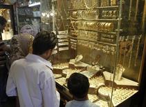 Сирийцы стоят перед витриной ювелирного магазина в Дамаске 8 сентября 2013 года. Цены на золото близки к шестинедельному минимуму и снизятся в марте из-за растущего оптимизма в отношении американской экономики и слабого спроса на физических рынках Азии. REUTERS/Khaled al-Hariri