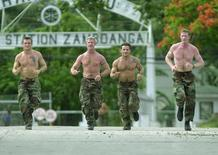 Four U.S. Navy seals jog at the Philippine Navy headquarters in Zamboanga City, in the southern Philippines June 17, 2002. REUTERS/str