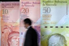 Un hombre pasa junto a una muestra de billetes de 10, 20 y 50 bolívares en la sede del Banco Central de Venezuela en Caracas, ago 22 2013. El Banco Central de Venezuela (BCV) anunció el lunes un incremento del encaje legal en 1 punto porcentual, a 21,5 por ciento, dentro de los intentos por disminuir la cantidad de dinero en circulación y contener la inflación anualizada de más 57 por ciento. REUTERS/Carlos Garcia Rawlins