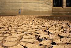 Um funcionário da Sabesp anda pela represa de Jaguari, atingida pela seca, em Bragança Paulista. A Sabesp decidiu reprogramar investimentos de 2014 e vai contingenciar 700 milhões de reais de seu orçamento neste ano para se concentrar na garantia de abastecimento de água em um dos momentos de maior seca já atravessados pela região metropolitana de São Paulo. 31/01/2014 REUTERS/Nacho Doce