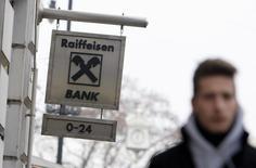 Человек проходит мимо вывески Raiffeisen Bank International в Будапеште 17 января 2014 года. Европейские банки, прежде всего австрийские, подвержены российским рискам более американских или азиатских, сообщило рейтинговое агентство Fitch Ratings, оценив возможные потери как вполне подъемные. REUTERS/Bernadett Szabo