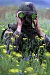 Американский солдат из возглавляемого НАТО миротворческого подразделения смотрит в бинокль в сербском селении Муховац в секторе B зоны безопасности рядом с Косово 24 мая 2001 года. Генсек НАТО сказал во вторник, что не видит свидетельств отхода российских войск от границы с Украиной, который анонсировал Кремль. PHOTO/Reuters