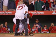 Mar 31, 2014; Anaheim, CA, USA; Former Angels outfielder Vladimir Guerrero (L) helps Angels hitting coach Don Baylor (R) after being injured during the first-pitch ceremony in the of an opening day baseball game at Angel Stadium of Anaheim. Robert Hanashiro-USA TODAY Sports