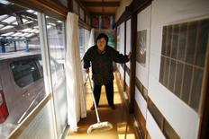 Kimiko Koyama, 69, who evacuated from the Miyakoji area of Tamura three years ago, dusts off her house after she returned to her home with her husband Toshio, 76, in Tamura, Fukushima prefecture April 1, 2014. REUTERS/Issei Kato