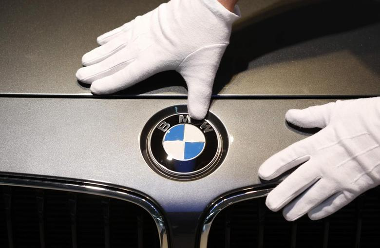 A man cleans a BMW logo before the annual news conference of German premium automaker BMW in Munich March 19, 2014. REUTERS/Michaela Rehle