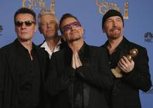"""Adam Clayton, Bono, Larry Mullen, Jr., and The Edge (L to R), from the band U2, pose backstage with their award for Best Original Song for """"Ordinary Love"""" from the film """"Mandela: Long Walk to Freedom"""" at the 71st annual Golden Globe Awards in Beverly Hills, California January 12, 2014. REUTERS/Lucy Nicholson"""