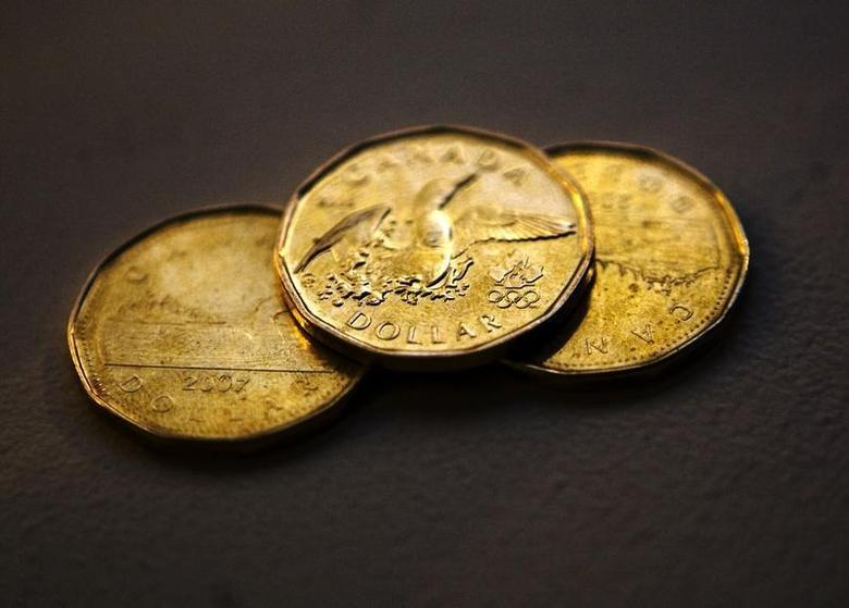 Canadian loonies, one dollar coins, are displayed in this posed photograph in Toronto, October 10, 2008. REUTERS/Mark Blinch