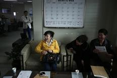 Gao Yiai (C), 35, from China's Shandong province, reacts as she talks with a driving instructor at a driving school in Siheung March 27, 2014. Chinese shoppers already have a seemingly insatiable appetite for South Korean pop music, TV dramas, cosmetics and fashion. Now they're after another must-have item: a driver's licence. In China, would-be drivers can wait. REUTERS/Kim Hong-Ji