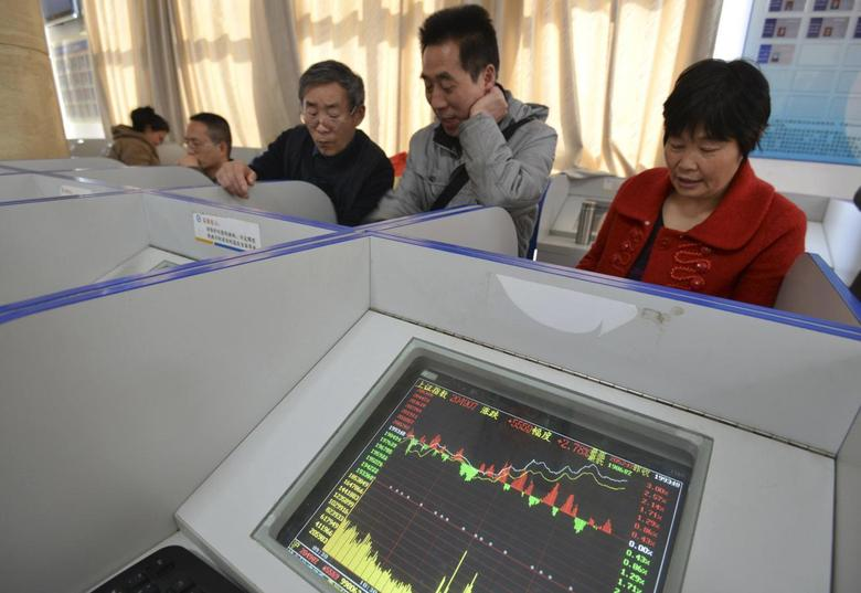 Investors look at computer screens showing stock information at a brokerage house in Fuyang, Anhui province March 21, 2014. REUTERS/China Daily