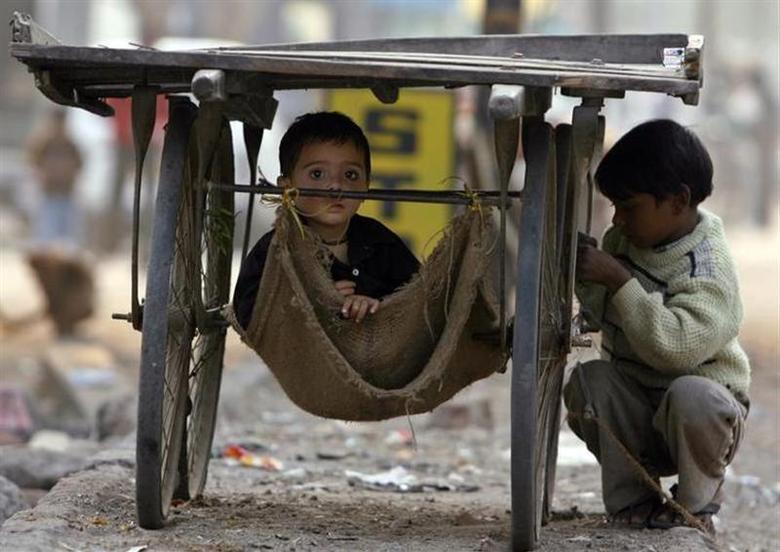 Children of slum dwellers play under a pushcart in New Delhi December 19, 2006. REUTERS/Ahmad Masood/Files