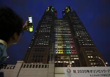 "A visitor takes photos of Tokyo Metropolitan Government Building illuminated in the Olympic colors before an event titled ""Tokyo 2020 Host City Welcoming Ceremony"", upon the delegation's return, in Tokyo September 10, 2013. REUTERS/Issei Kato"