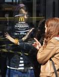 """Мужчина показывает женщине, что ресторан McDonald's в Симферополе закрыт, 4 апреля 2014 года. Сеть ресторанов McDonalds в четверг приостановила работу 3 точек, находящихся в Крыму, который Москва после проведения там референдума сделала частью РФ, """"в связи с независящими от компании причинами"""", говорится на сайте украинского подразделения сети. REUTERS/Stringer"""