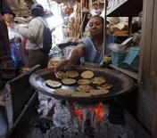 Una persona vende tortillas en un puesto callejero en Ibarra, Ecuador, mayo 9 2013. La tasa anual de inflación Ecuador se aceleró a 3,11 por ciento en los últimos 12 meses hasta marzo frente a igual periodo del año previo, informó el viernes la agencia oficial de estadística. REUTERS/Guillermo Granja