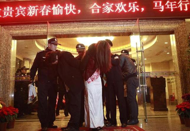 4月4日、中国沿岸部の広東省東莞市は「世界の工場」である以外に「性都」としても知られるが、今年2月に行われた大規模な売春摘発により大きな経済的打撃に見舞われている。写真は同市で行われた摘発で連行される人たち。2月撮影(2014年 ロイター)