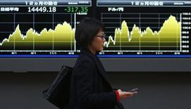 Женщина проходит мимо экранов, отображающих колебания индекса Nikkei и курса иены, в Токио 20 февраля 2014 года. Азиатские фондовые рынки завершили торги понедельника разнонаправленно под воздействием местных факторов. REUTERS/Yuya Shino