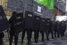 Policiais protegem a entrada da sede da Petrobras durante protesto contra o leilão do campo de petróleo de Libra, no Rio de Janeiro. Para 78 por cento dos brasileiros, existe corrupção na Petrobras e para 29 por cento deste contingente a corrupção na empresa é maior do que em outras estatais do país, de acordo com pesquisa Datafolha divulgada nesta segunda-feira. 21/10/2013. REUTERS/Pilar Olivares