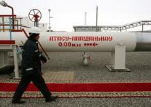 Рабочий идет вдоль нефтепровода в Атасу 15 декабря 2005 года. Казахстан, тесно взаимодействующий в энергетической сфере со своим партнером по Таможенному союзу Россией, ищет запасные маршруты для экспорта нефти в случае расширения пакета санкций со стороны ЕС против РФ, сообщил глава Миннефтегаза Узакбай Карабалин. REUTERS/Shamil Zhumatov