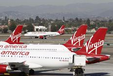 A Virgin America jet takes off past other aircraft parked at Terminal 3 as the terminal begins to reopen the day after a shooting incident occurred at Los Angeles airport (LAX), California November 2, 2013. REUTERS/David McNew