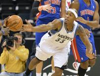 Minnesota Timberwolves' Dante Cunningham (R) and Detroit Pistons' Will Bynum (12) reach for a rebound during the first half of their NBA pre-season basketball game in Winnipeg in this file photo from October 24, 2012. REUTERS/Fred Greenslade/Files