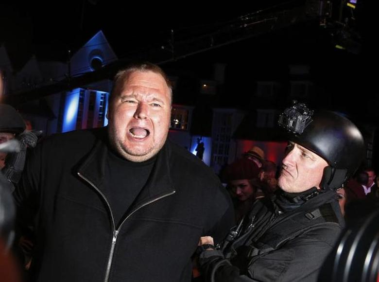 An actor in police costume mock-arrests Megaupload founder Kim Dotcom (L) as he launches his new file sharing site ''Mega'' in Auckland January 20, 2013. REUTERS/Nigel Marple/Files
