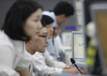 Валютные дилеры в торговом зале банка в Сеуле 26 сентября 2011 года. Азиатские фондовые рынки, кроме Японии, выросли во вторник благодаря подъему отдельных отраслей. REUTERS/Lee Jae-Won