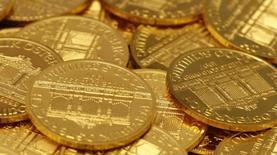 Золотые монеты в аукционном доме Dorotheum в Вене 16 апреля 2013 года. Цены на золото выросли более чем на 1 процент за счет технических покупок после пересечения отметки $1.300 и повышения привлекательности драгметалла как надежного вложения на фоне усиления напряженности на Украине. REUTERS/Leonhard Foeger