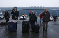 Люди ждут машину у терминала аэропорта Домодедово 26 декабря 2010 года. Минтранс РФ объявил два конкурса на общую сумму 15 миллиардов рублей на реконструкцию аэропорта Домодедово, включая строительство второй взлетно-посадочной полосы, следует из материалов на сайте госзакупок. REUTERS/Mikhail Voskresensky