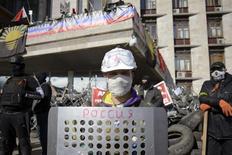 Пророссийский протестующий на баррикаде перед зданием областной администрации в Донецке 8 апреля 2014 года. Госсекретарь США Джон Керри во вторник прямо обвинил российских агентов в активности сепаратистов на востоке Украины, сказав, что Москва, вероятно, пытается подготовить почву для военных действий, подобных крымским. REUTERS/Maks Levin