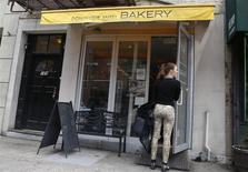 A woman waits to enter the Dominique Ansel Bakery is seen in New York April 8, 2014. REUTERS/Shannon Stapleton
