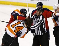 Apr 8, 2014; Sunrise, FL, USA; Linesman Pierre Racicot (65) tries to break up a fight between Florida Panthers defenseman Erik Gudbranson (44) and Philadelphia Flyers center Sean Couturier (14) in the first period at BB&T Center. Robert Mayer-USA TODAY Sports
