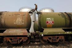 Рабочий проверяет цистерны на нефтяном терминале на окраине Калькутты 27 ноября 2013 года. Цены на нефть снижаются на фоне усиления геополитической напряженности на Украине и неожиданно резкого повышения запасов нефти в США. REUTERS/Rupak De Chowdhuri