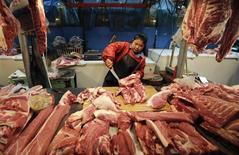 Женщина режет свинину на рынке в Пекине 11 января 2013 года. Один из крупнейших мировых производителей свинины китайская WH Group Ltd рассчитывает привлечь порядка $4,3 миллиарда от продажи новых акций в ходе IPO в Гонконге, сказали Рейтер источники, знакомые с ситуацией. REUTERS/Jason Lee