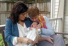 Valeria Tanco (L), and Sophy Jesty pose with their new baby girl, Emilia, at their home in Knoxville, Tennessee April 7, 2014. REUTERS/Wade Payne