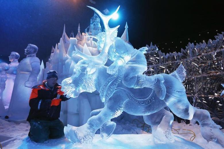 Sculptor Sergey Aseev of Russia carves a sculpture based on Disney's newest movie ''Frozen'' at the Snow and Ice Sculpture Festival in Bruges November 20, 2013. REUTERS/Francois Lenoir/Files