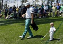 U.S. golfer Ryan Moore and his son Tucker (R) walk along the third hole during the Par 3 contest ahead of the Masters golf tournament at the Augusta National Golf Club in Augusta, Georgia April 9, 2014. REUTERS/Mike Blake