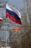 Флаг РФ на фоне газового факела у подземного хранилища Черноморнефтегаза в Глебовке, Крым 9 апреля 2014 года. Европа готовится сократить закупки российского газа более чем на четверть к концу десятилетия на фоне ухудшения отношений с Россией из-за Украины. REUTERS/Stringer