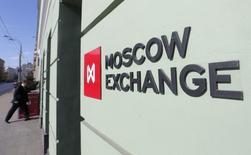 Человек у входа в здание Московской биржи 14 марта 2014 года. Российские фондовые индексы последовали в четверг примеру Уолл-стрит, которая с оптимизмом восприняла опубликованные накануне протоколы мартовского заседания ФРС. REUTERS/Maxim Shemetov