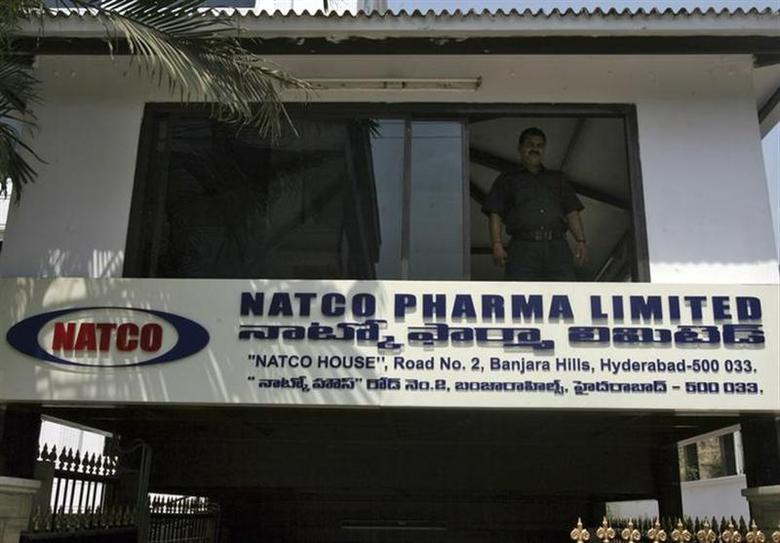 A private security guard looks out from a window of the head office of Natco in Hyderabad March 13, 2012. REUTERS/Krishnendu Halder/Files