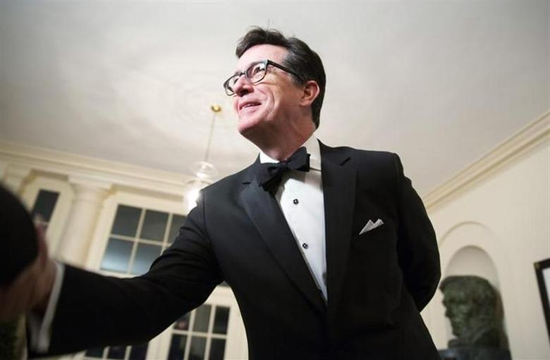 Comedian Stephen Colbert greets a reporter as he arrives for the State Dinner being held for French President Francois Hollande at the White House in Washington on February 11, 2014. REUTERS/Joshua Roberts/Files