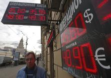 Мужчина проходит мимо пункта обмена валют в Москве 20 февраля 2014 года. Рубль утром пятницы отметился на минимуме двух недель против бивалютной корзины и евро на фоне текущего бегства от риска и укрепления единой европейской валюты, из-за сохраняющегося давления со стороны украинского кризиса, возобновления покупок валюты Минфином РФ. REUTERS/Maxim Shemetov