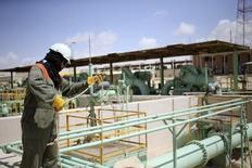 Рабочий на территории нефтяного терминала в Эз-Зуетине 7 апреля 2014 года. Цены на нефть снижаются, так как рынок ждет возобновления поставок из Ливии, но напряженные отношения России с Западом из-за Украины продолжают поддерживать котировки. REUTERS/Esam Omran Al-Fetori