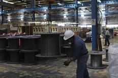 Un trabajador sostiene un cable de acero en una planta de la acería TIM en Huamantla, México, oct 11 2013. La actividad industrial de México creció en febrero un 0.3 por ciento contra el mes previo gracias al impulso del sector de la construcción, la minería y las industrias manufactureras, dijo el viernes el instituto de estadísticas. REUTERS/Tomas Bravo