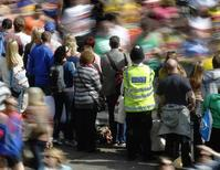A police officer observes runners and crowd during the London Marathon April 21, 2013. REUTERS/Luke MacGregor