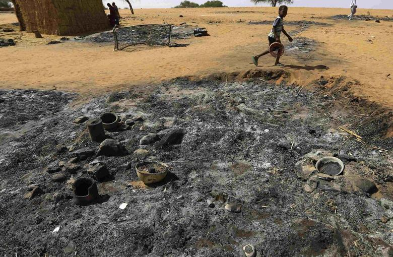 A boy walks past a house that was burned down during an attack by rebels in Mellit town in North Darfur March 24, 2014. REUTERS/Mohamed Nureldin Abdallah