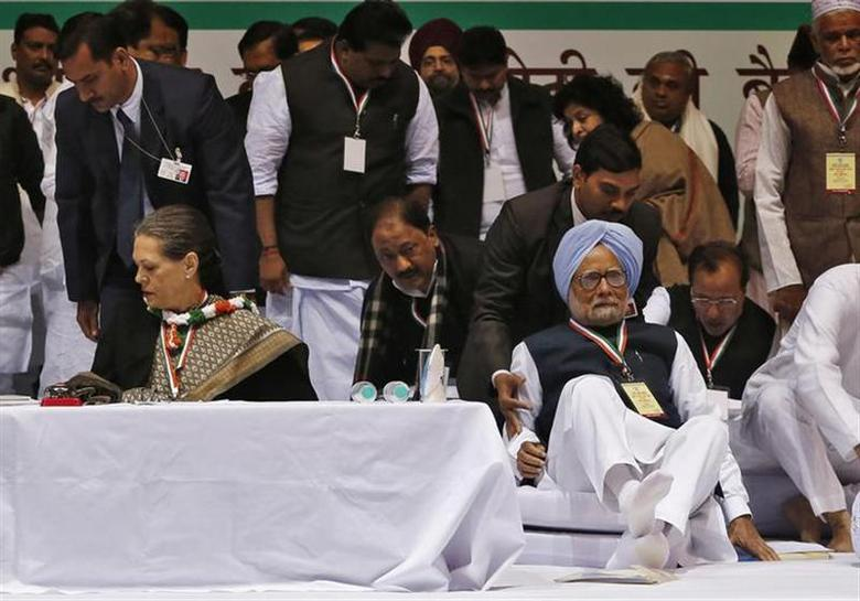 Prime Minister Manmohan Singh (wearing turban) is helped by his bodyguard as he loses his balance to sit beside Sonia Gandhi, chief of ruling Congress party, during the All India Congress Committee (AICC) meeting in New Delhi January 17, 2014. REUTERS/Adnan Abidi/Files