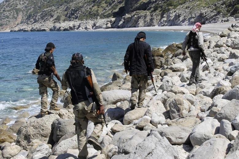 Rebel fighters walk with their weapons at the beach in Latakia province near the town of Kasab April 5, 2014. Picture taken April 5, 2014. REUTERS/Stringer