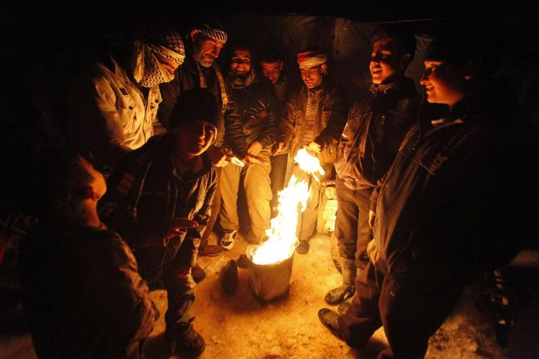 Syrian refugees from the town of Qara gather around a fire to keep themselves warm in a Syrian refugee camp on the Lebanese border town of Arsal, in eastern Bekaa Valley December 12, 2013. REUTERS/Alia Haju