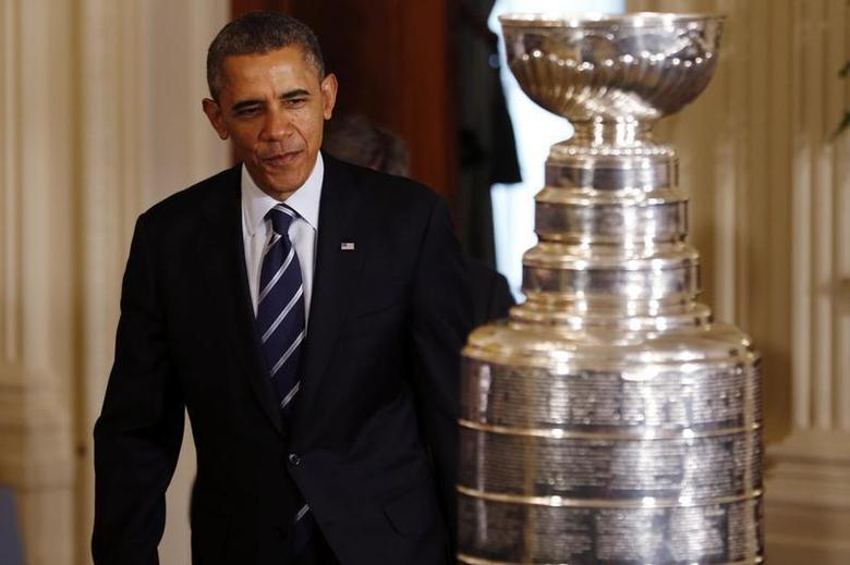 United States president Barack Obama enters the East Room behind the Stanley Cup prior to an event honoring the 2013 NHL Stanley Cup champion Chicago Blackhawks at The White House. Mandatory Credit: Geoff Burke-USA TODAY Sports
