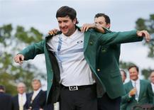 Masters winner Bubba Watson, has 2013 winner Adam Scott (R), present him his green jacket after winning the Masters golf tournament at the Augusta National Golf Club in Augusta, Georgia April 13, 2014. REUTERS/Mike Blake