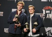"""Actors Sam Claflin (L) and Josh Hutcherson pose backstage with their award for Best Movie of the Year and Hutcherson's award for Best Male Performance for the film """"The Hunger Games: Catching Fire"""" at the 2014 MTV Movie Awards in Los Angeles, California April 13, 2014. REUTERS/Danny Moloshok"""